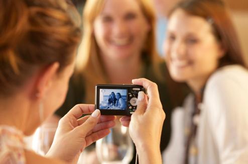 Une fille photographie ses copines avec un compact