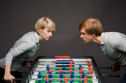 Un homme et une femme jouent au babyfoot