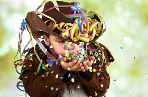 Un petit garçon déguisé souffle sur des confettis