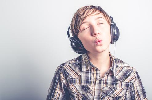 Un enfant siffle en écoutant la musique avec un casque