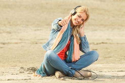 Une fille écoute sa musique assise sur la plage
