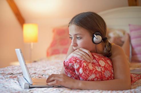 Une fille regarde un film sur un lecteur DVD portable