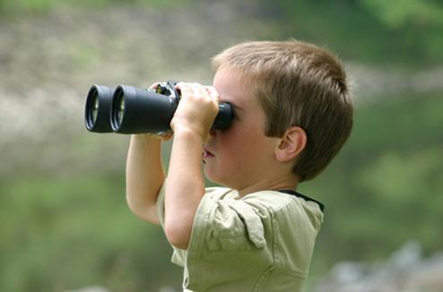Un enfant regarde au loin avec ses jumelles