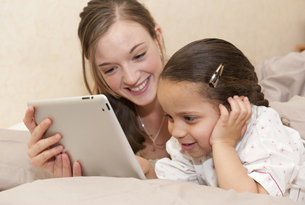 Parent qui accompagne son enfant sur sa tablette tactile
