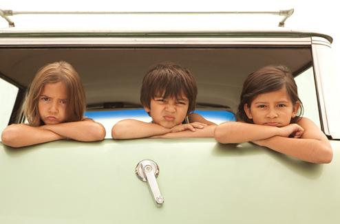Trois enfants font la moue dans une voiture