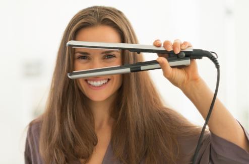 Une femme avec un lisseur à cheveux
