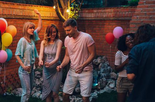 Un groupe d'amis danse dans le jardin