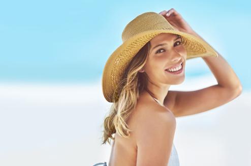 Une fille avec un chapeau à la plage