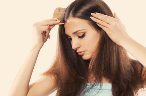 Une fille se coiffe avec un peigne