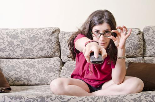 Une fille ajuste ses lunettes en regardant la TV