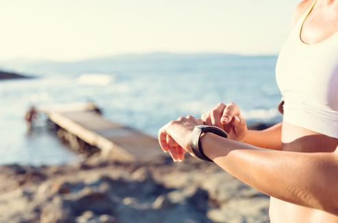 Une fille avec une montre de sport à la plage