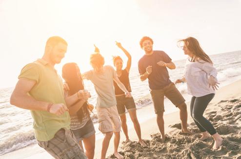 Un groupe d'amis danse sur la plage