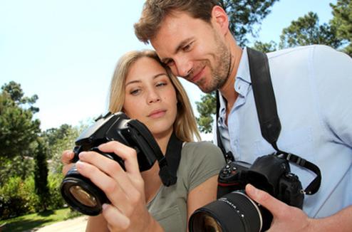 Un homme et une femme s'entraînent à la photo avec des reflex