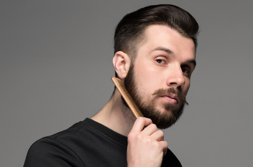 Un homme se peigne la barbe