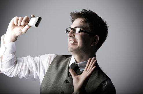 Un homme fait un selfie avec un appareil photo compact