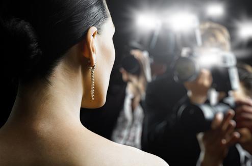 Une fille pose devant des photographes
