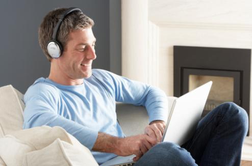Un homme avec son ordinateur et un casque