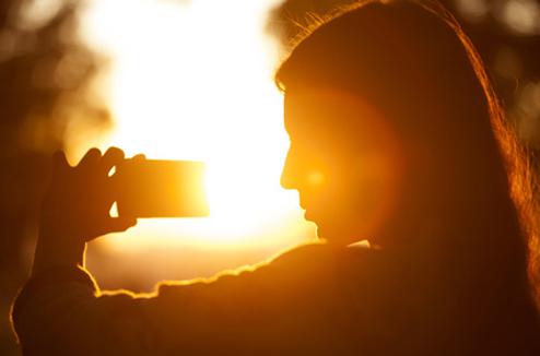 Une fille prend une photo en plein soleil