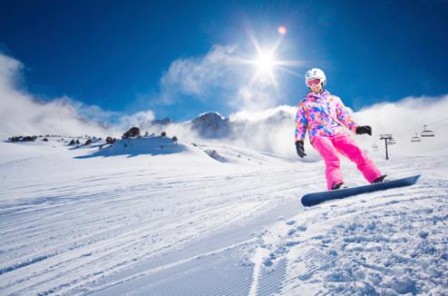 Une fille en snowboard descend la piste