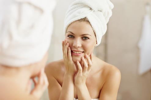 Une fille se regarde dans un miroir et prend soin de sa peau