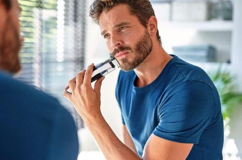 Un homme tond sa barbe avec la tondeuse Philips Beardtrimmer