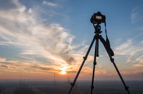 Un reflex sur un trépied photo au coucher du soleil