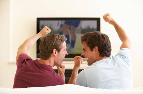 Deux hommes contents devant un match à la TV
