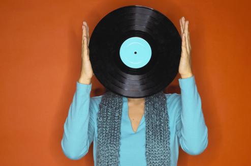 Une femme tient un vinyle devant son visage