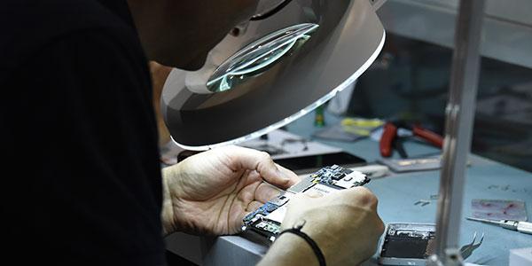 Technicien qui répare un smartphone